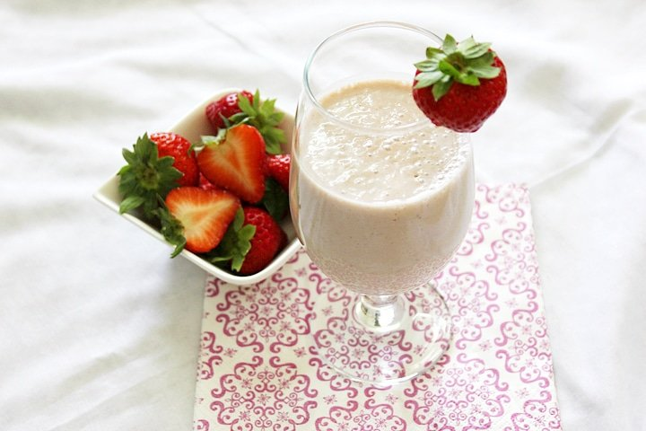 banana strawberry oats smoothie with fresh strawberries on the side.