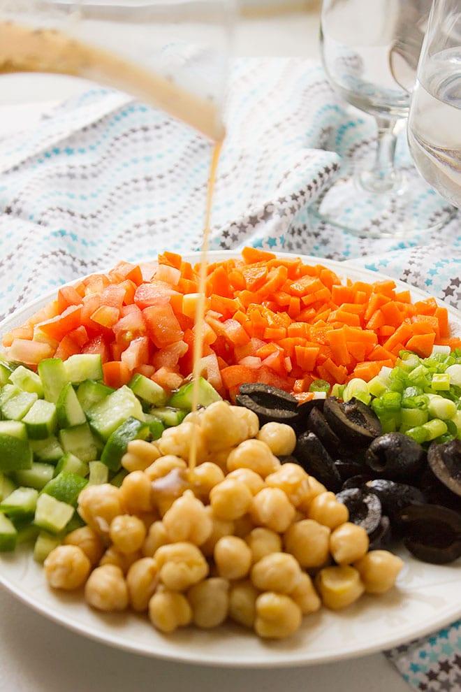 Close up shot of pouring dressing over Chickpea Salad. #salad #vegan #healthysald #saladrecipe #recipe