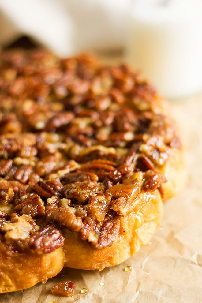 Close image showing toasted pecans on sticky cinnamon rolls.