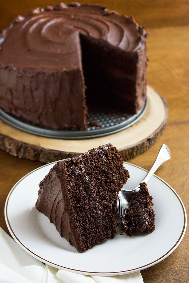 A slice of devilish chocolate cake with a fork on the side.