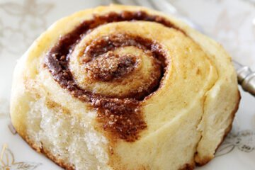 Small image of light cinnamon rolls on a plate.