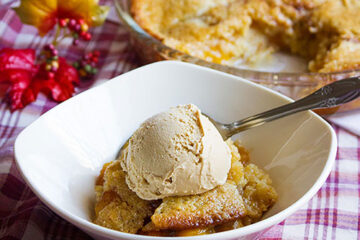 small image of peach cobbler in a bowl.