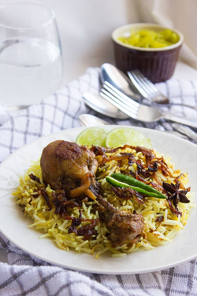 Hyderabadi chicken biryani served with glass of water on the side.