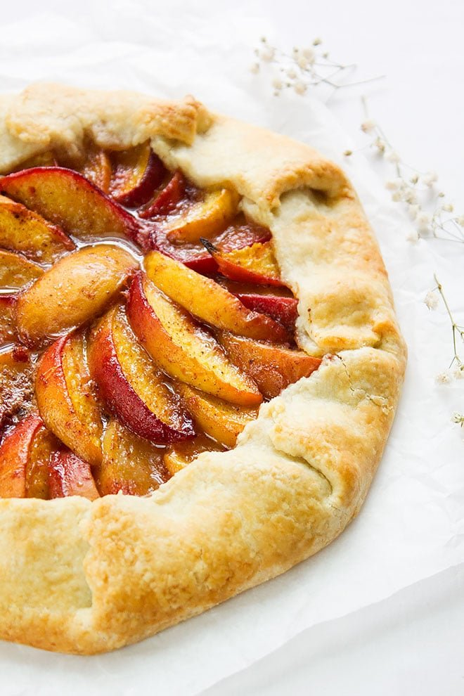 Close up image of peach galette on parchment paper.