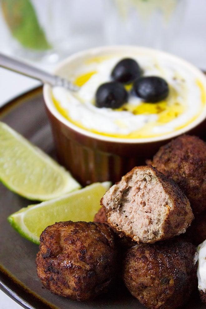 Side shot of Greek Meatballs half eaten and showing how tender it is.