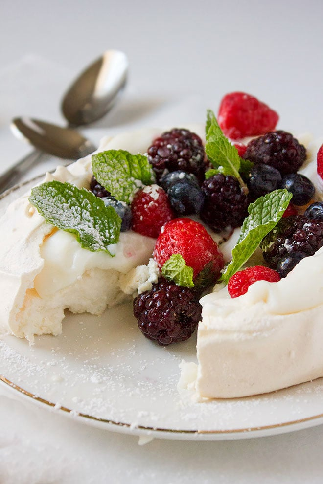 classic pavlova served in a plate with fresh fruits.