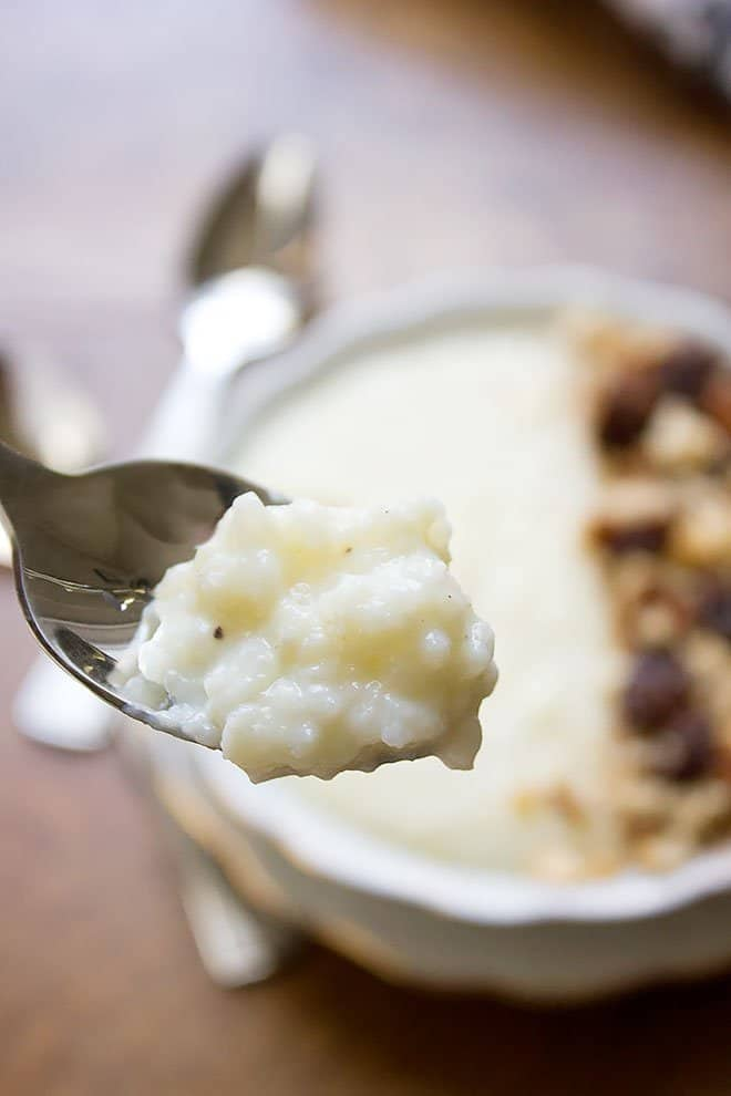 Close up shot of rice pudding in a spoon showing the creamy texture.