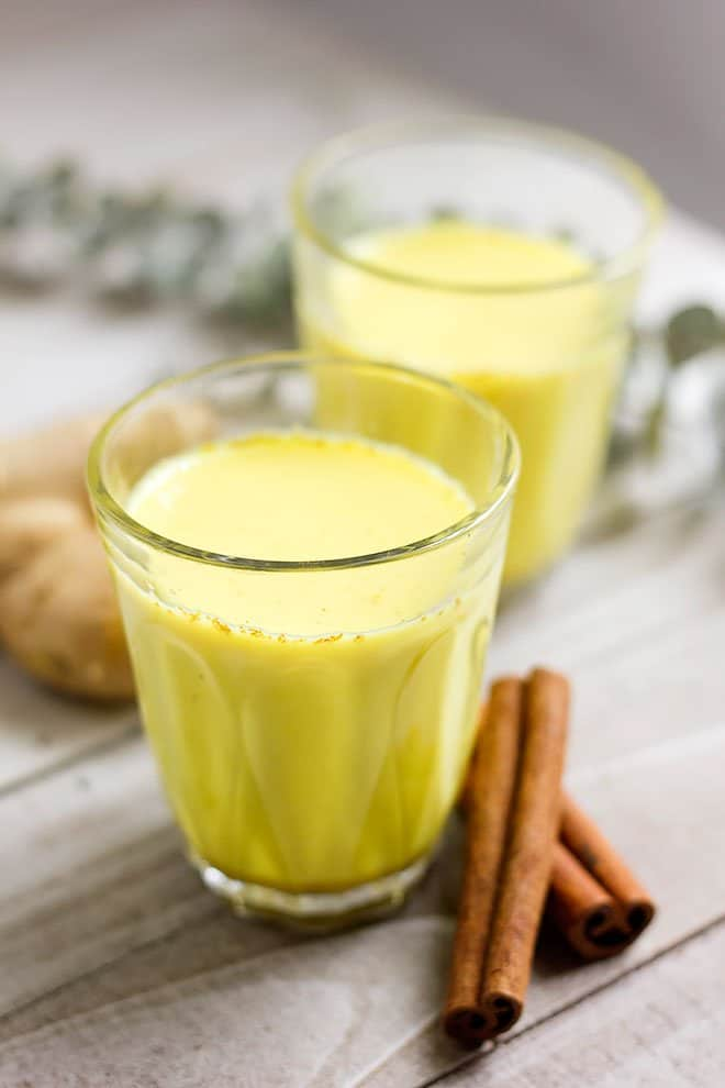 Golden milk in transparent glass with cinnamon on the side.