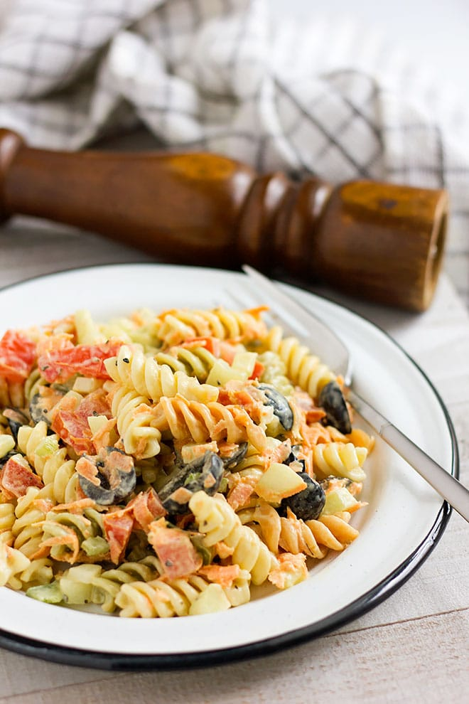 Pasta salad is served in a white plate ready to be eaten.