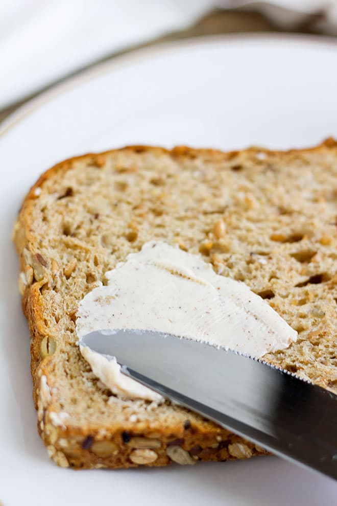 close up side shot of flavored butter spread on whole wheat bread