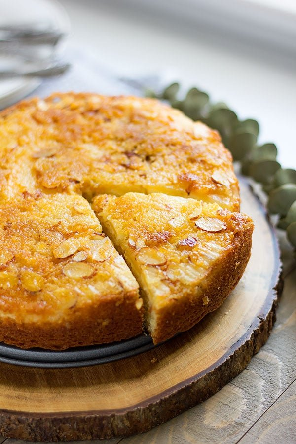 lemon cake with a slice cut and showing almond slices on top. #lemoncake #cakerecipe #cake #dessert #lemon