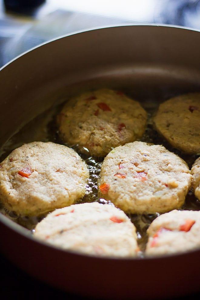 frying salmon patties in oil.