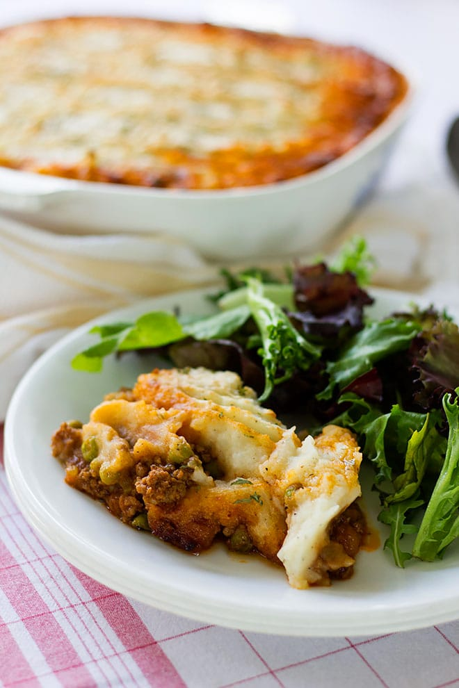 Shepherd's Pie served in a white plate with green vegetables.