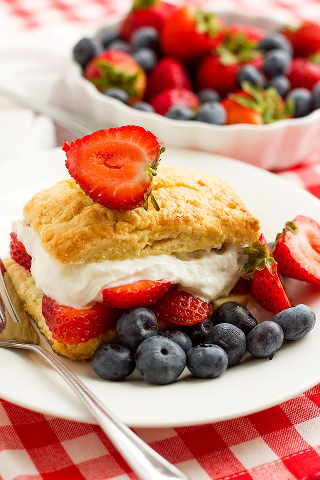 strawberry shortcake served on a plate with blueberries.