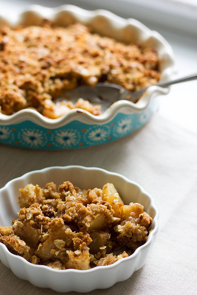 Apple crumble in a small bowl beside a bigger baking pan