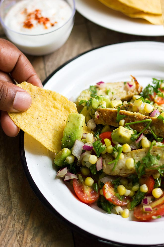 Scooping avocado chicken salad with tortilla chips