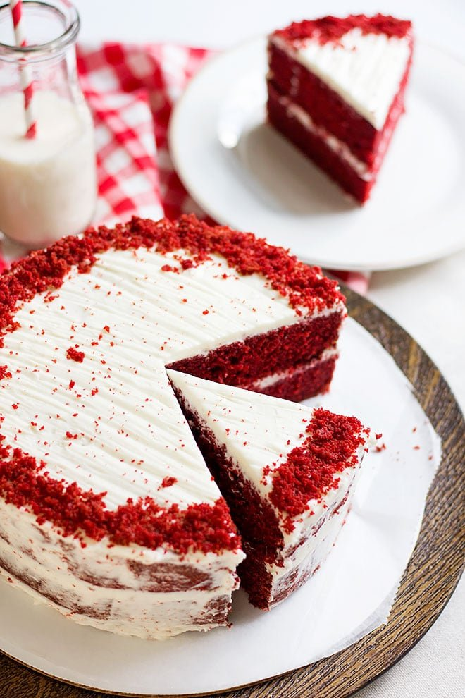 a whole red velvet cake and a slice on the side.