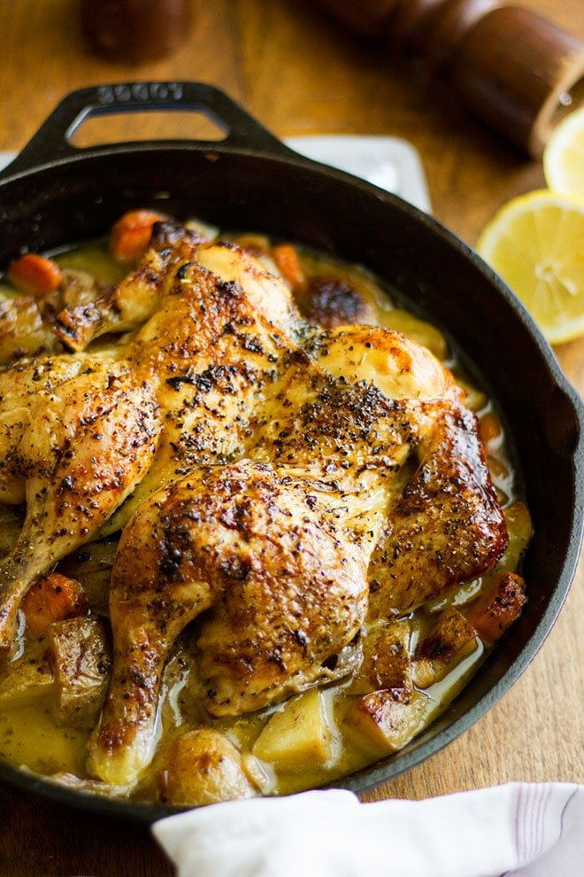 roast chicken served in black skillet with roasted vegetables.