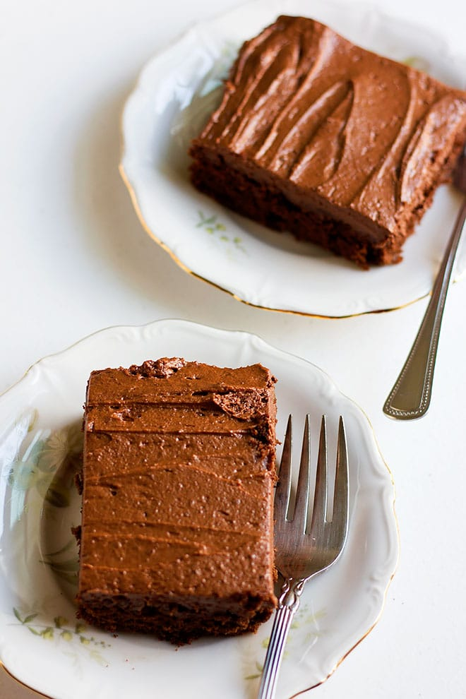 Two slices of chocolate cake in plates.
