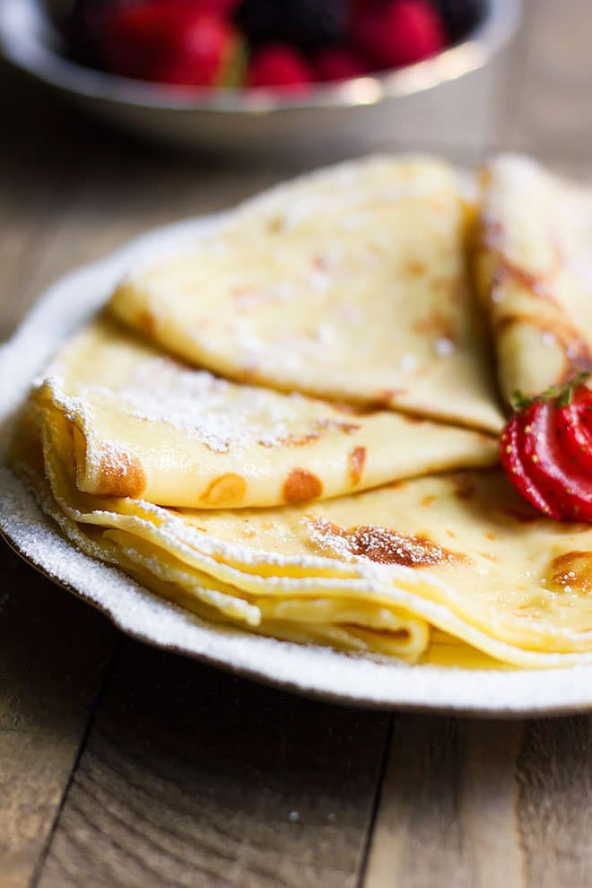Crepes served on a plate with icing sugar.
