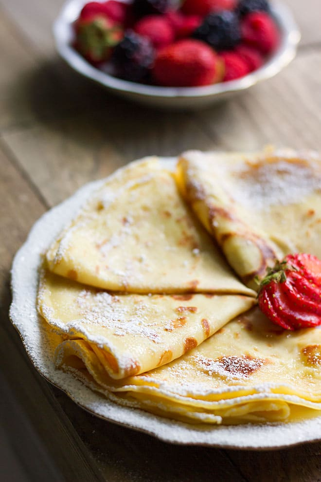 Crepes served in plate with strawberry slices in the middle.