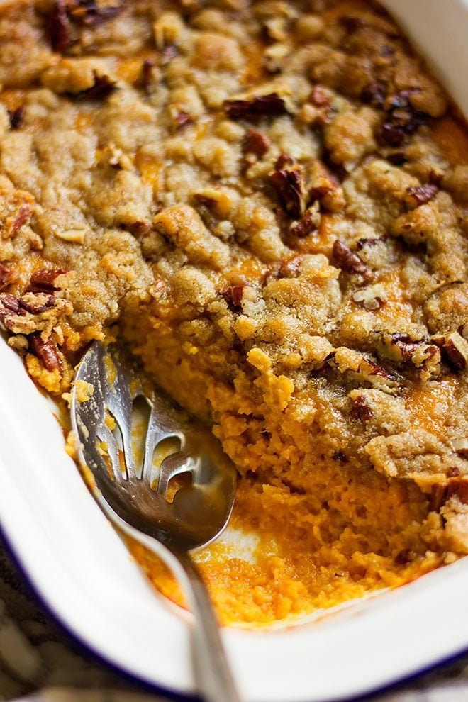 Serving sweet potato casserole from baking dish.