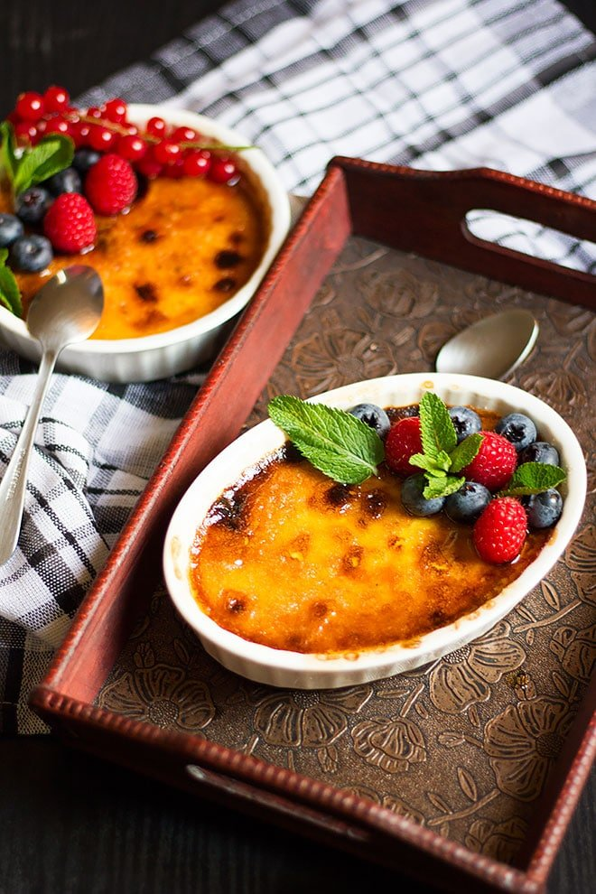 Two ramekins with Creme Brulee Topped with berries.