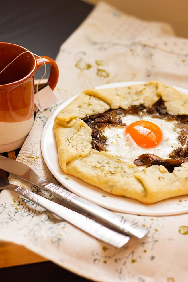 Side image of mushroom and onion galette with a mug on the side.