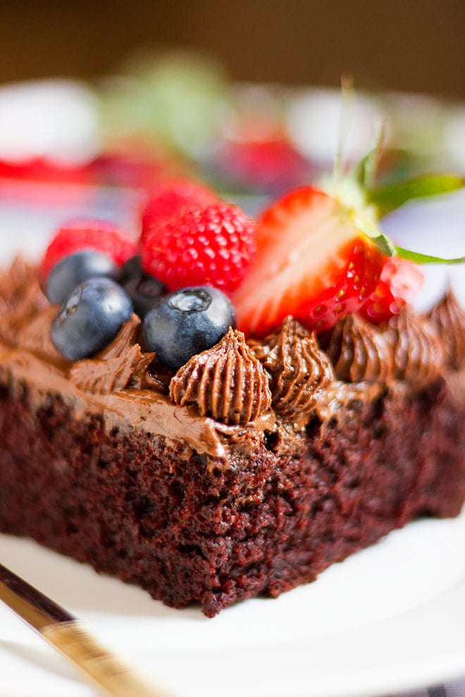 Close up chocolate cake with chocolate frosting and berries.