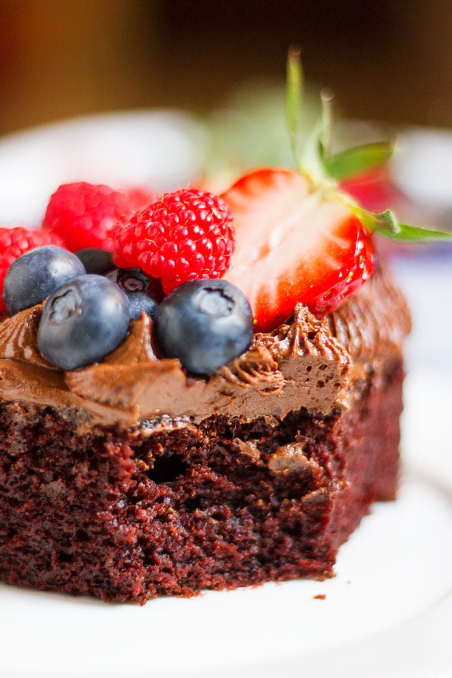 Moist egg free chocolate cake frosted and topped with fruit.