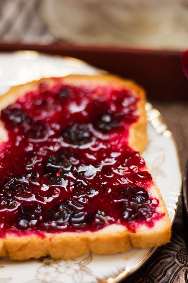 Berry jam spread over bread and showing few blueberries.