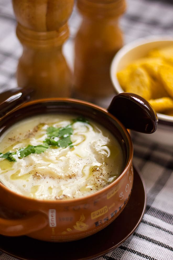 Freshly made hot creamy potato soup in a brown bowl.