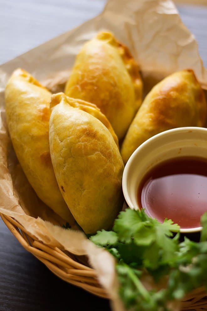 empanadas served with red sweet sauce on the side.