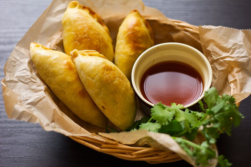 Four large empanadas filled with chicken.