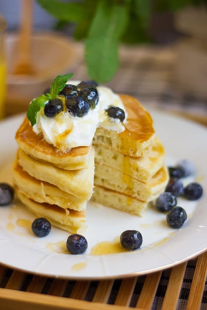 Yogurt pancakes topped with cream and blueberries.