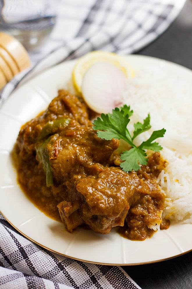 Achari gosht served in a plate with plain rice.
