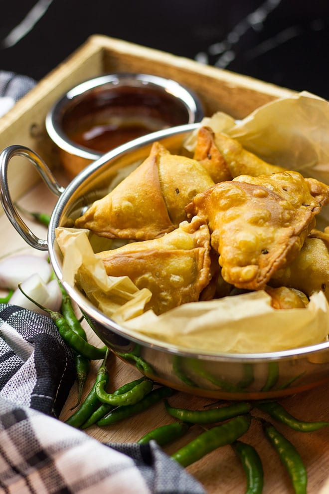 Chicken samosa served in a stainless steal bowl.