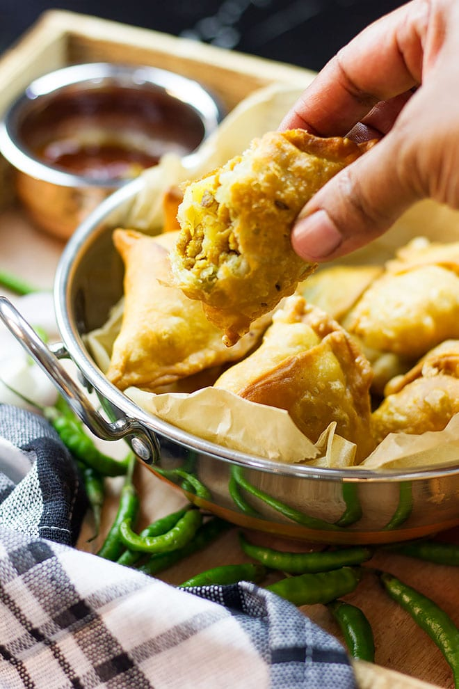 Holding chicken samosa to show the filling.