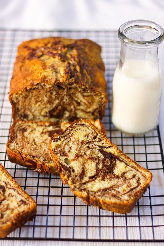 Showing marble cake loaf on a cooling rack with milk on the side.