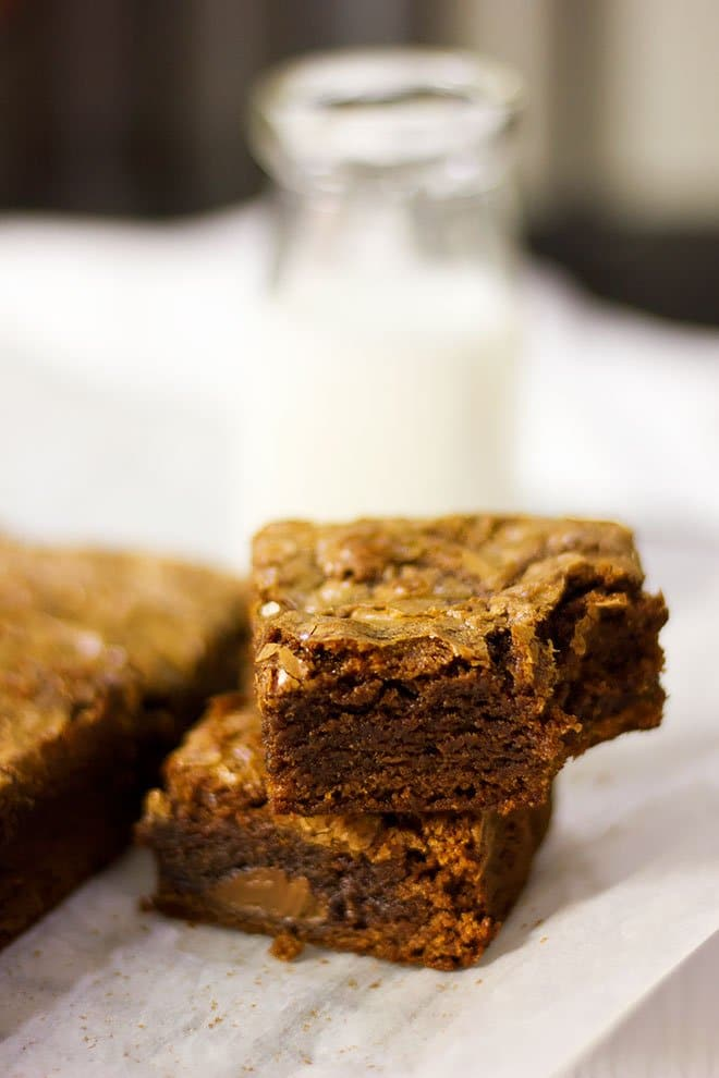 Milk bottle behind two squares of Nutella brownies.