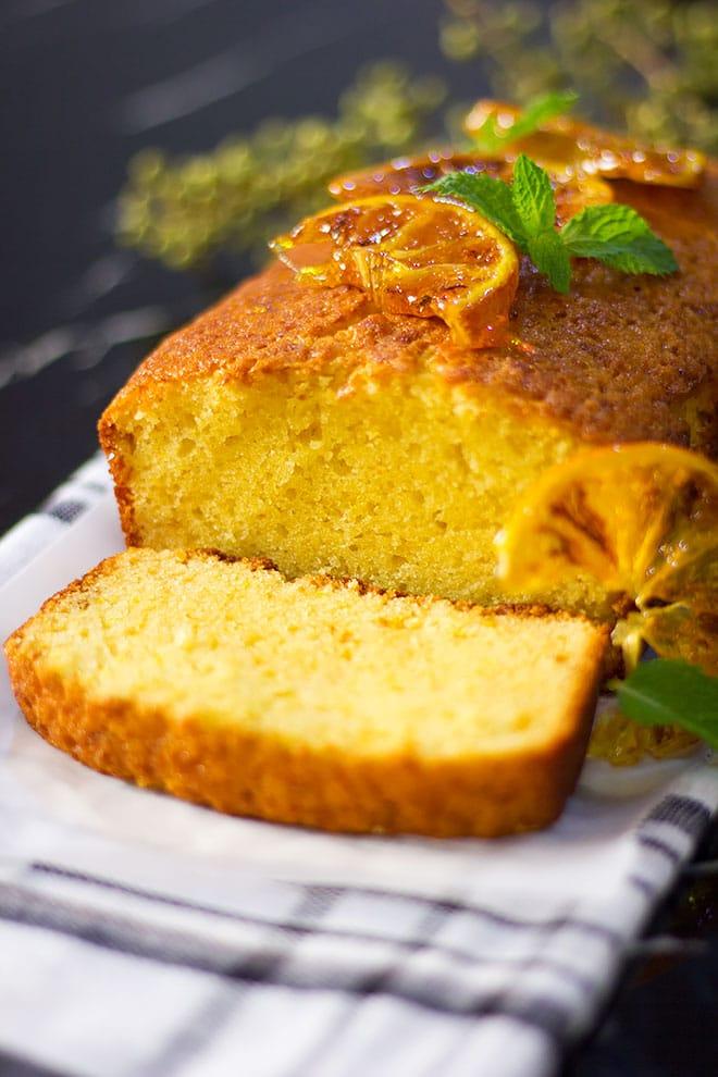 Orange cake loaf topped with candid orange.