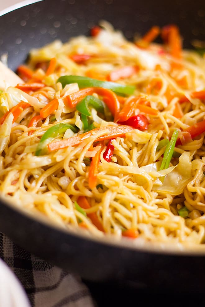 Vegetable chow mein in a black wok.
