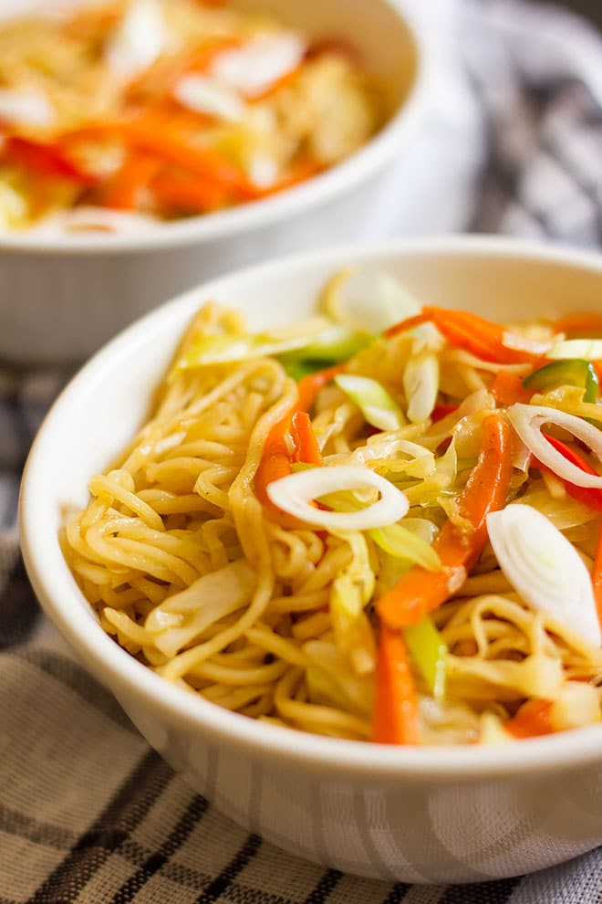 Close up image of vegetable chow mein served in a white bowl.