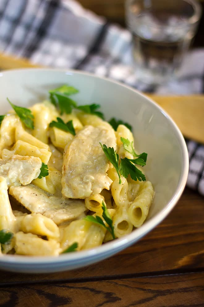 Chicken alfredo sprinkled with parsley.