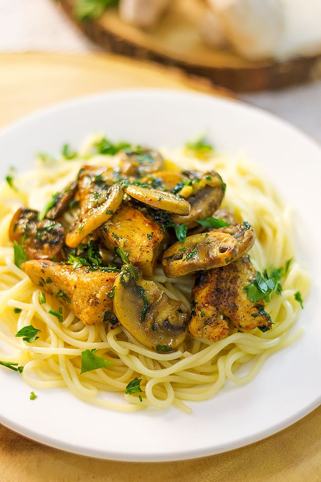 Close up image of Golden chicken breast chunks over spaghetti.