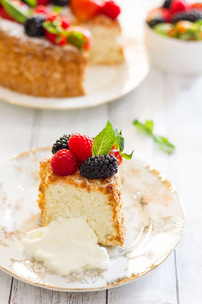 A slice of angel food cake with cream on the side.