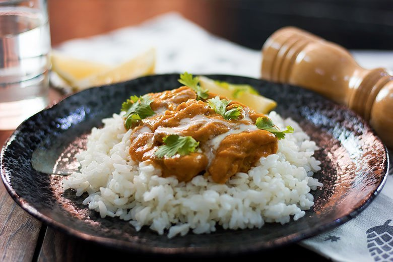 Close up image of butter chicken served in black plate.