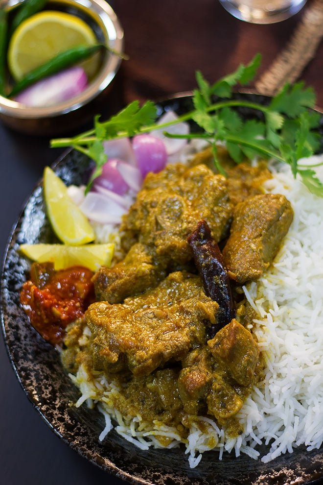 Side image of tender lamb in gravy served with rice.