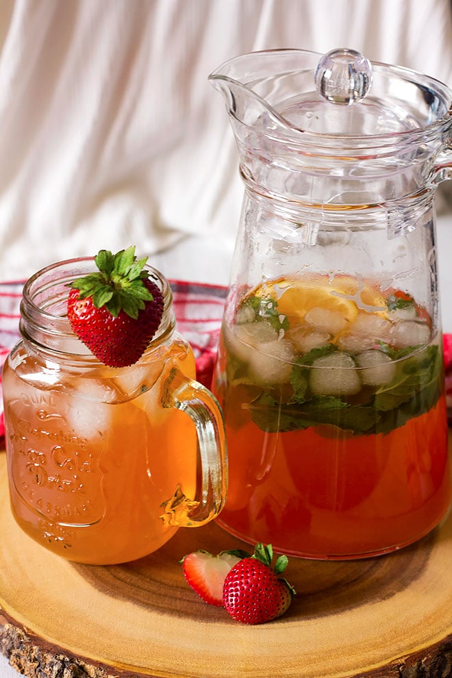 A pitcher and a glass full of strawberry lemonade.