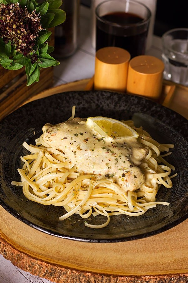 Tender chicken breast served with pasta on black plate.